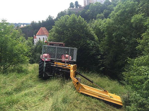 Traktor mit Mähwerk auf einer Wiese