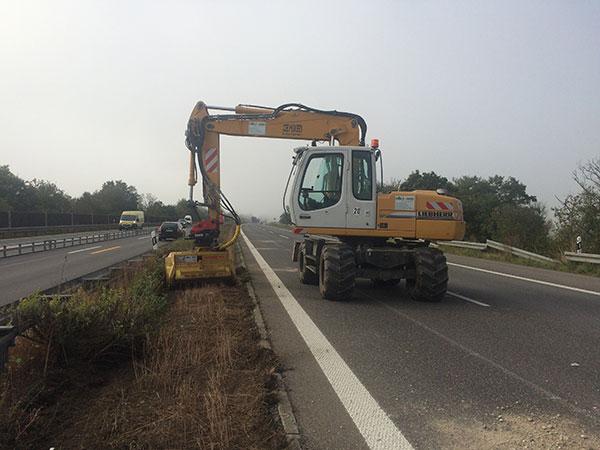 Mulcharbeiten mit einem Bagger auf der Autobahn