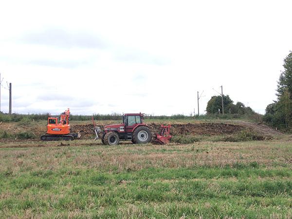 Mulcharbeiten mit Bagger und Traktor auf einem Feld