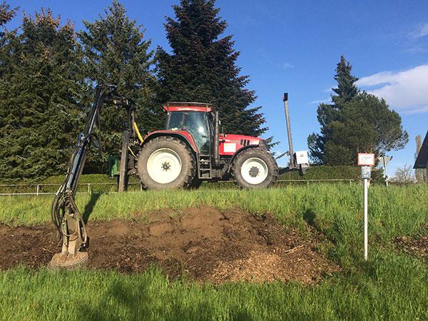 Wurzelstockfräsen an einer Böschung mit einem Traktor